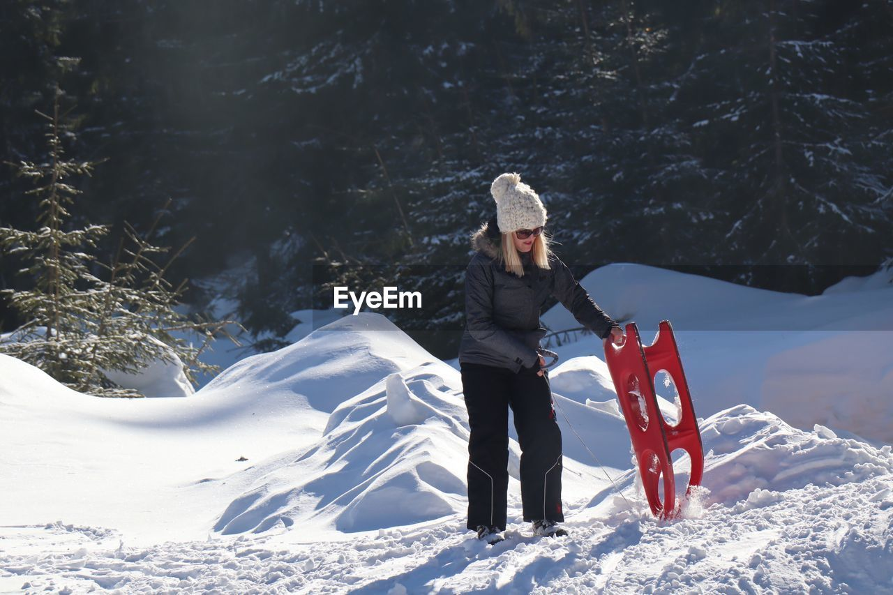 Full length of woman with sled standing on snow covered land