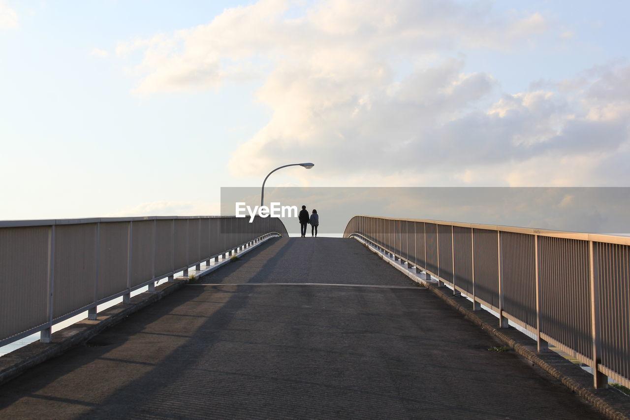 Rear View Of Friends Walking On Footbridge Against Sky