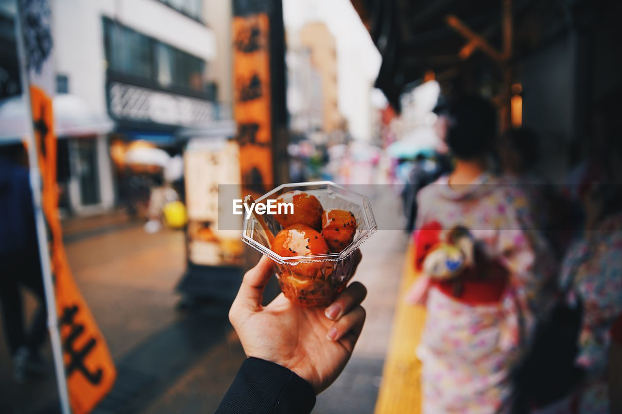 human hand, one person, food and drink, holding, real people, hand, focus on foreground, lifestyles, food, leisure activity, human body part, glass, freshness, drink, city, refreshment, incidental people, adult, household equipment, temptation, finger