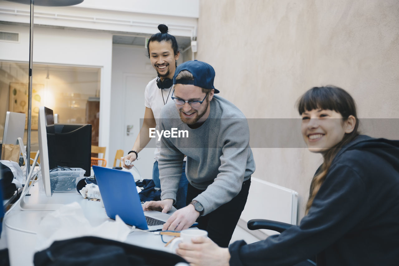 men, office, real people, young men, young adult, cooperation, technology, computer, adult, communication, table, working, males, smiling, business, sitting, business person, businessman, teamwork, professional occupation, wireless technology, using laptop, new business, coworker