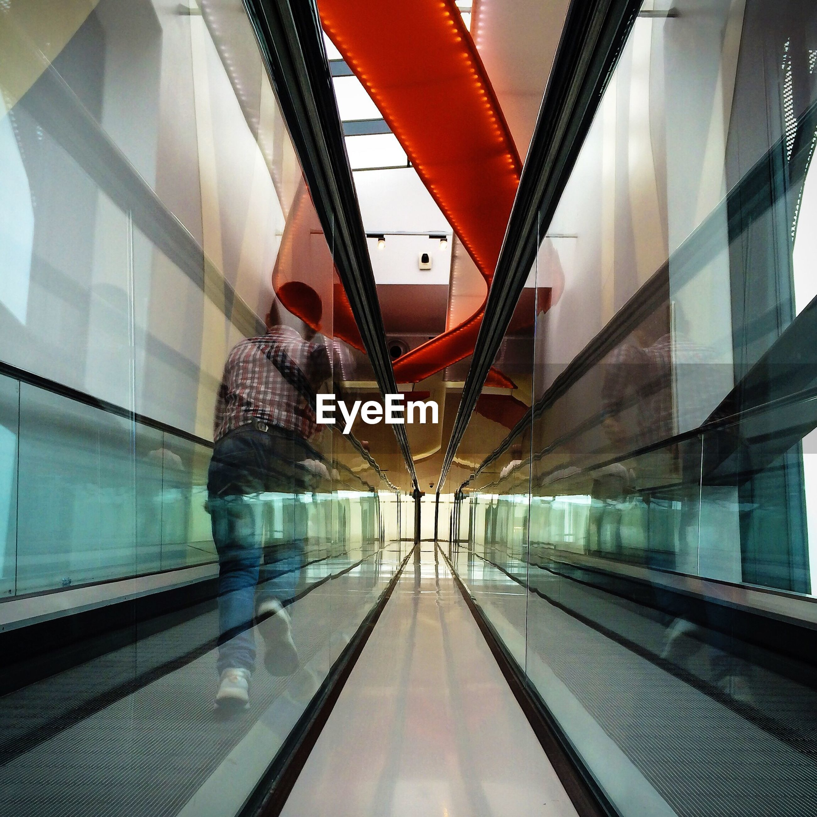 Rear view of boy running on moving walkway at shopping mall