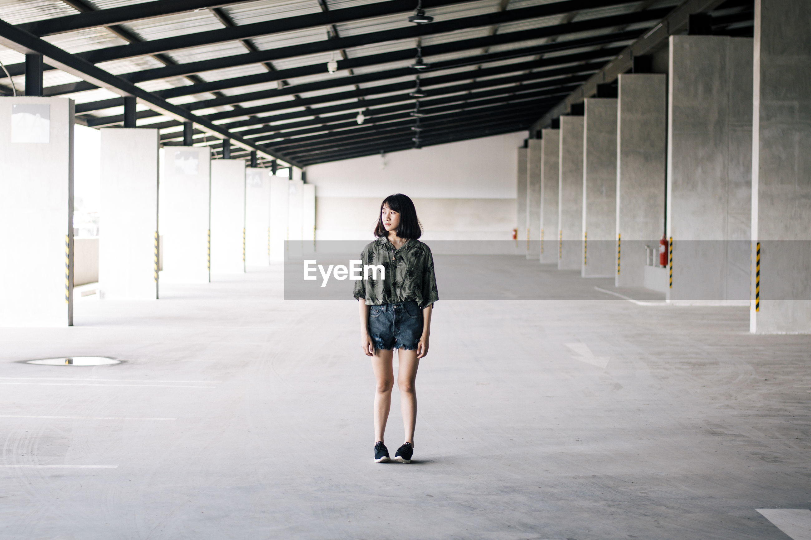 Full length of woman standing in corridor of building