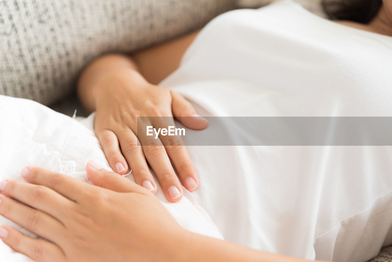 Midsection of woman with stomachache lying on sofa at home