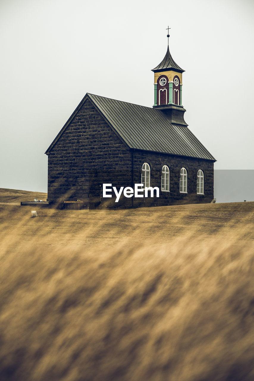 Exterior of black church on field against clear sky