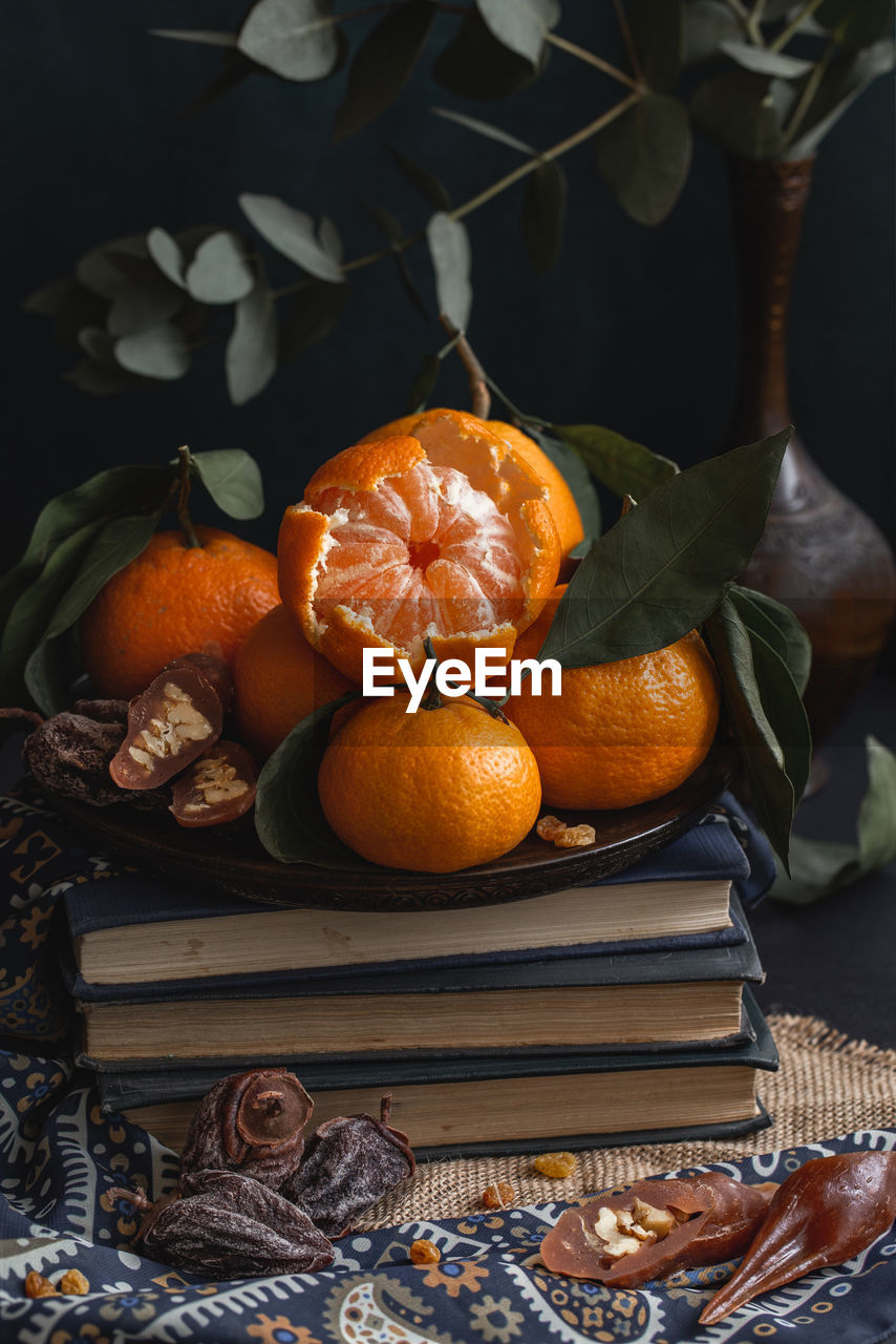 Close-up of orange fruits in plate on table