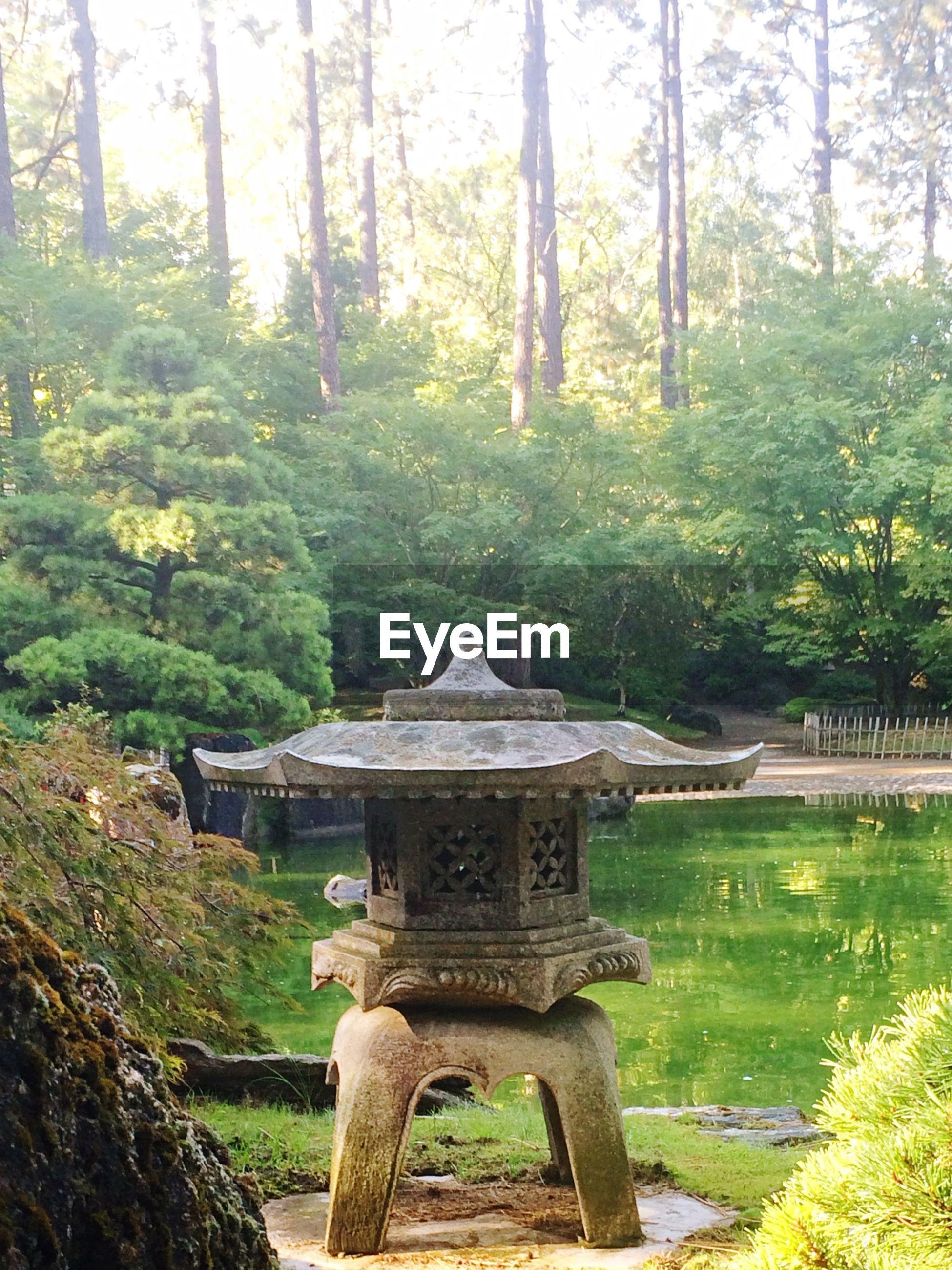 Stone lantern by pond in garden