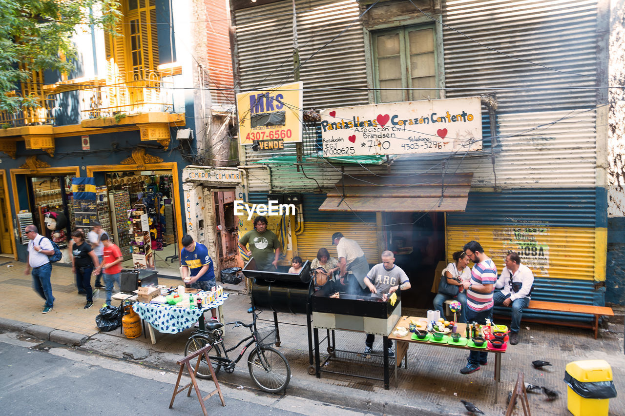 building exterior, real people, architecture, built structure, large group of people, sidewalk cafe, men, women, restaurant, city, outdoors, lifestyles, table, day, cafe, city life, food and drink, leisure activity, sitting, awning, food, full length, adult, people