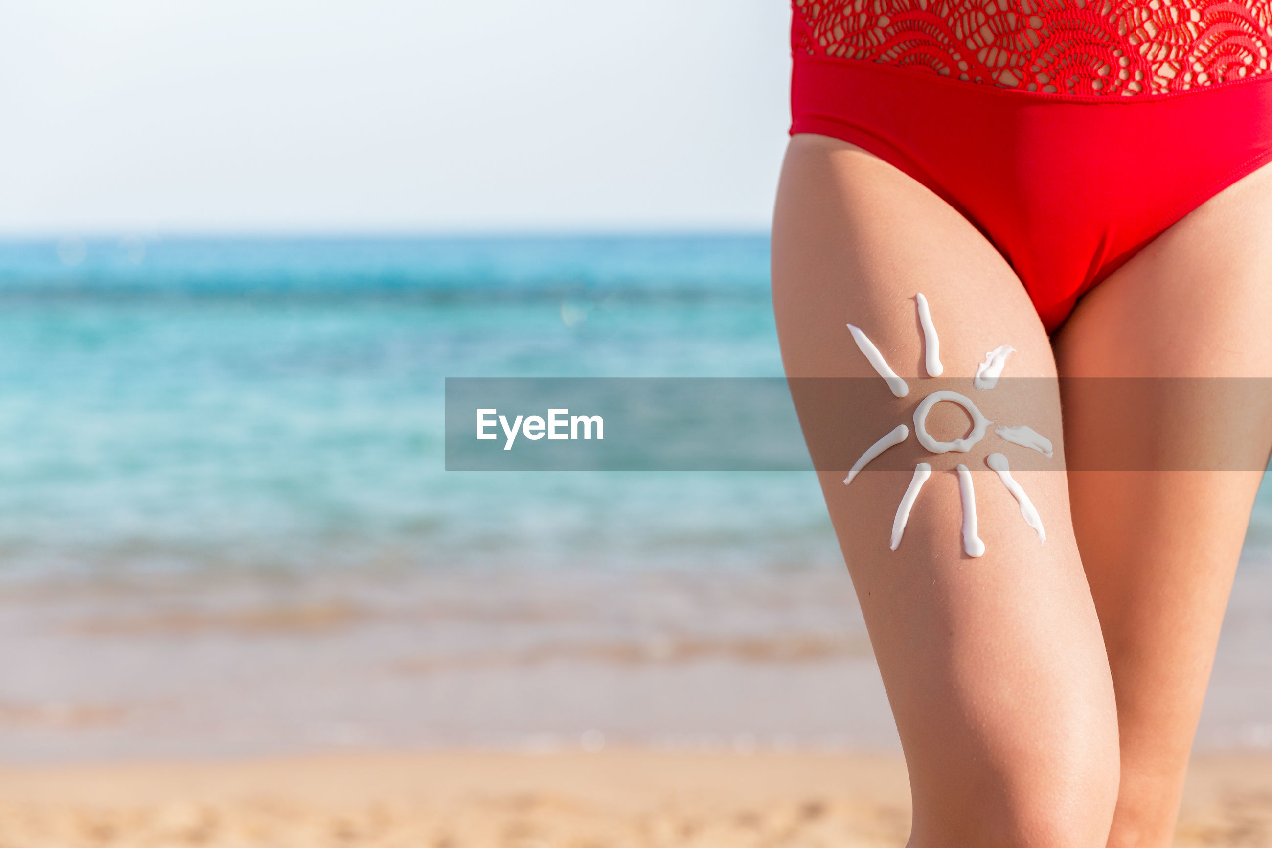 Midsection of woman with sun shape on thigh