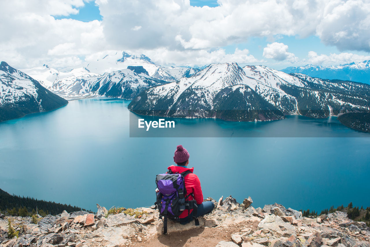 Rear view of backpacker sitting by lake against snowcapped mountains