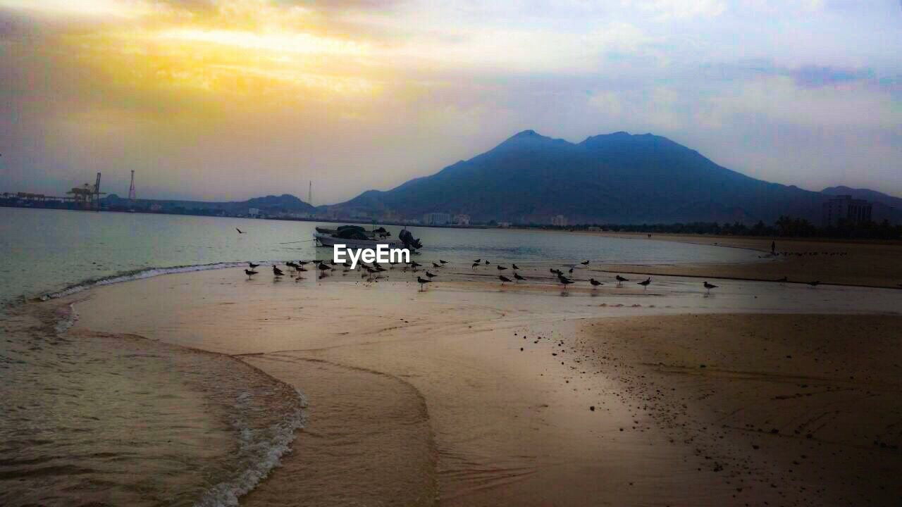 water, scenics, beauty in nature, nature, sky, tranquility, sand, sea, sunset, tranquil scene, mountain, beach, outdoors, cloud - sky, no people, mountain range, nautical vessel, day