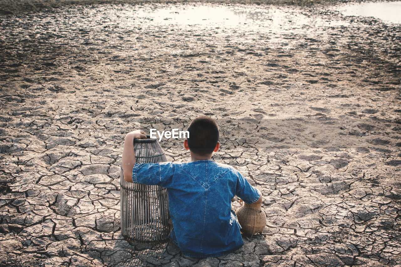 High Angle View Of Boy Sitting On Field During Drought
