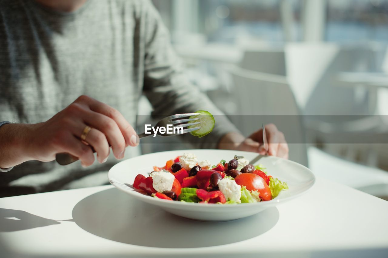 Midsection Of Person Eating Salad In Restaurant