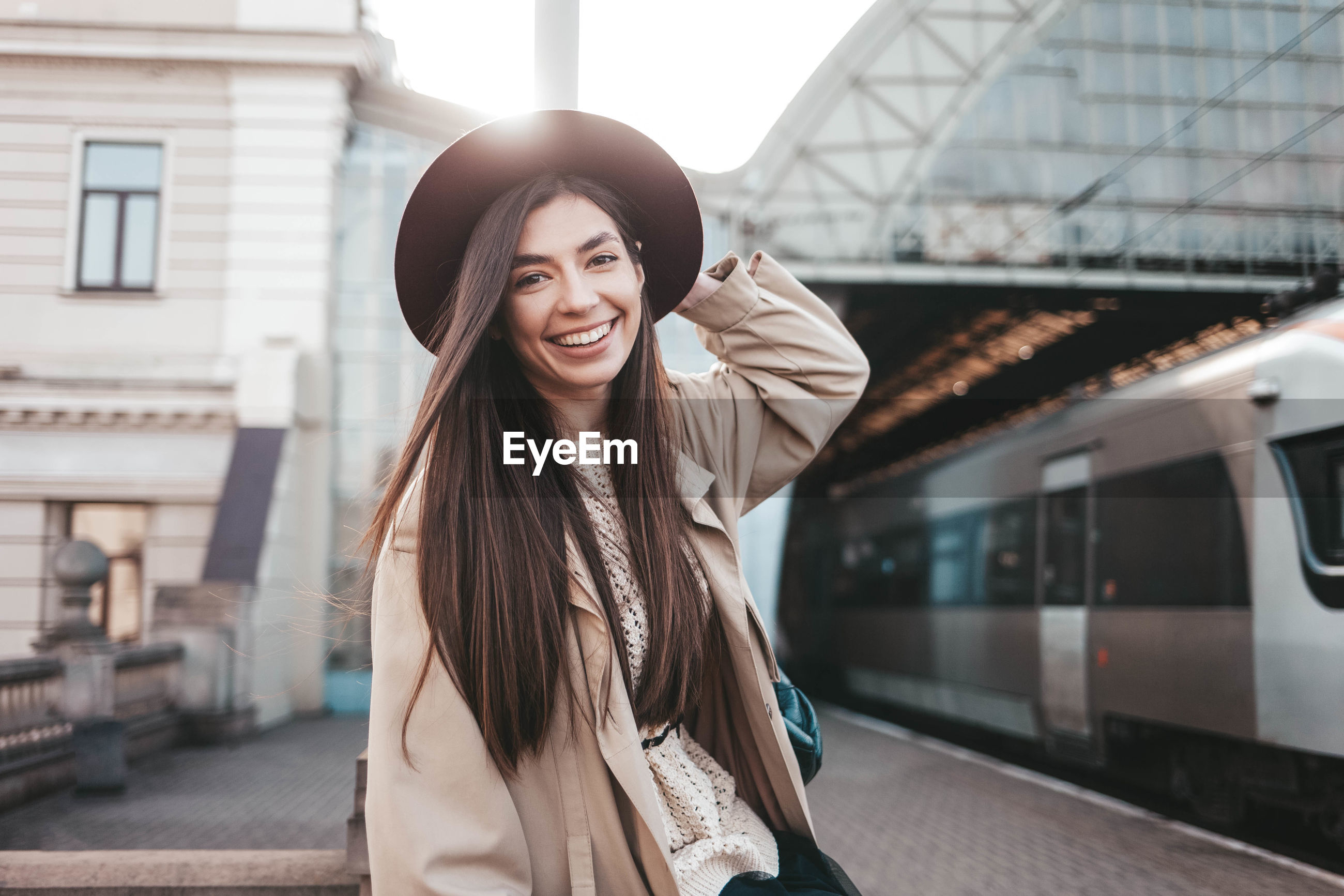 PORTRAIT OF BEAUTIFUL YOUNG WOMAN STANDING AT RAILROAD STATION