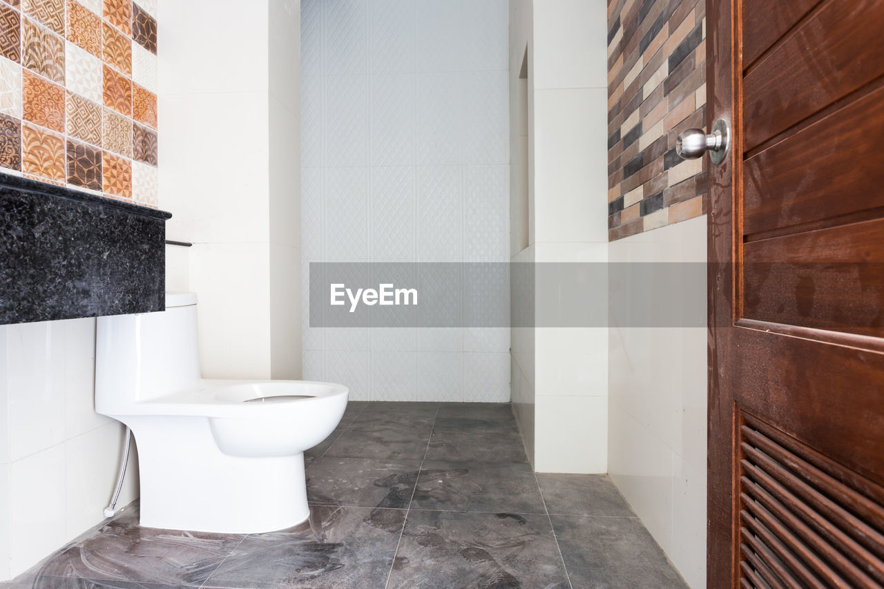 bathroom, domestic bathroom, indoors, toilet, home interior, hygiene, toilet bowl, flooring, domestic room, no people, home, white color, architecture, tile, wall - building feature, built structure, modern, seat, building, door, tiled floor, luxury, clean