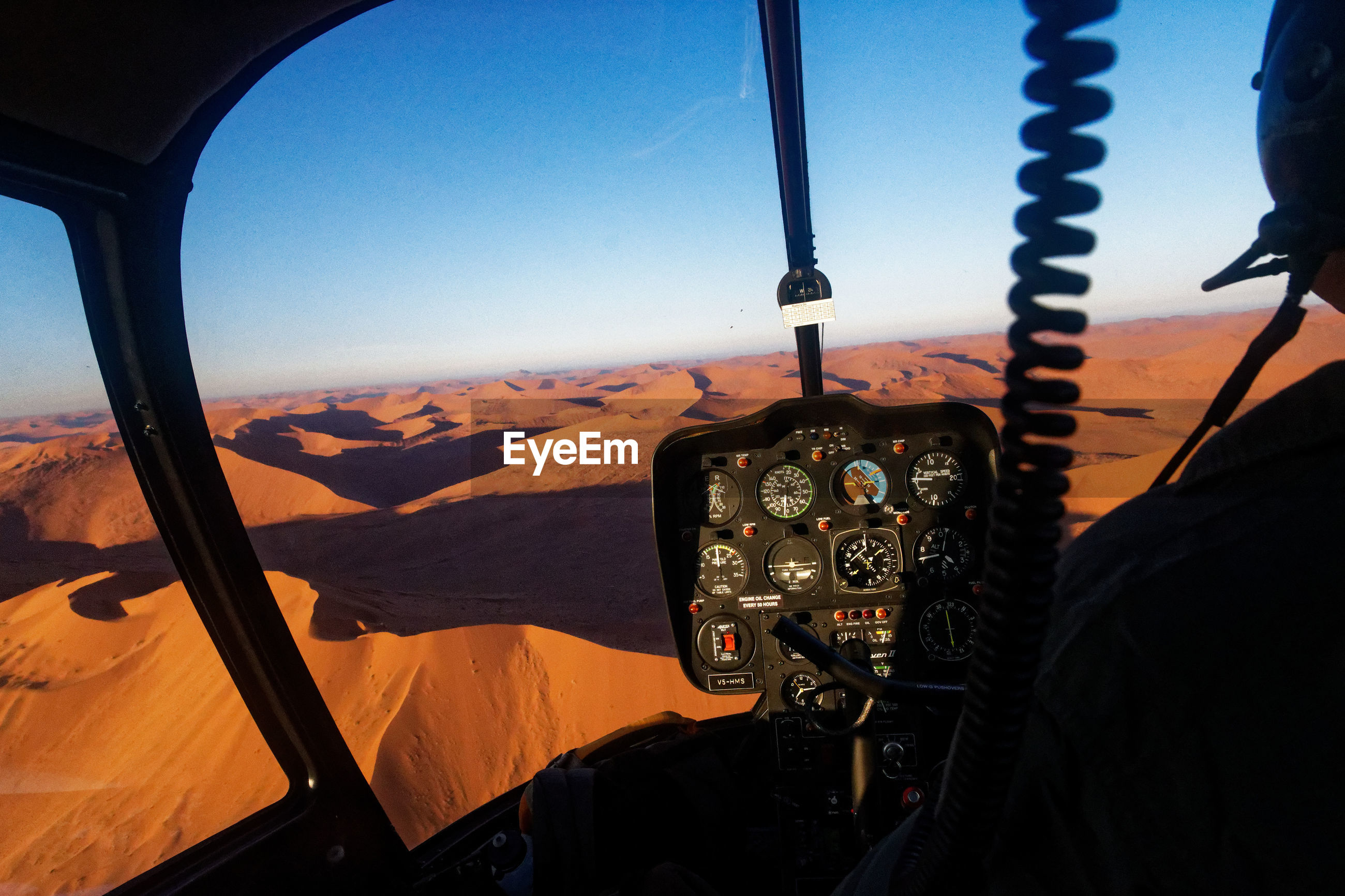 Cropped image of pilot flying airplane at desert against clear blue sky
