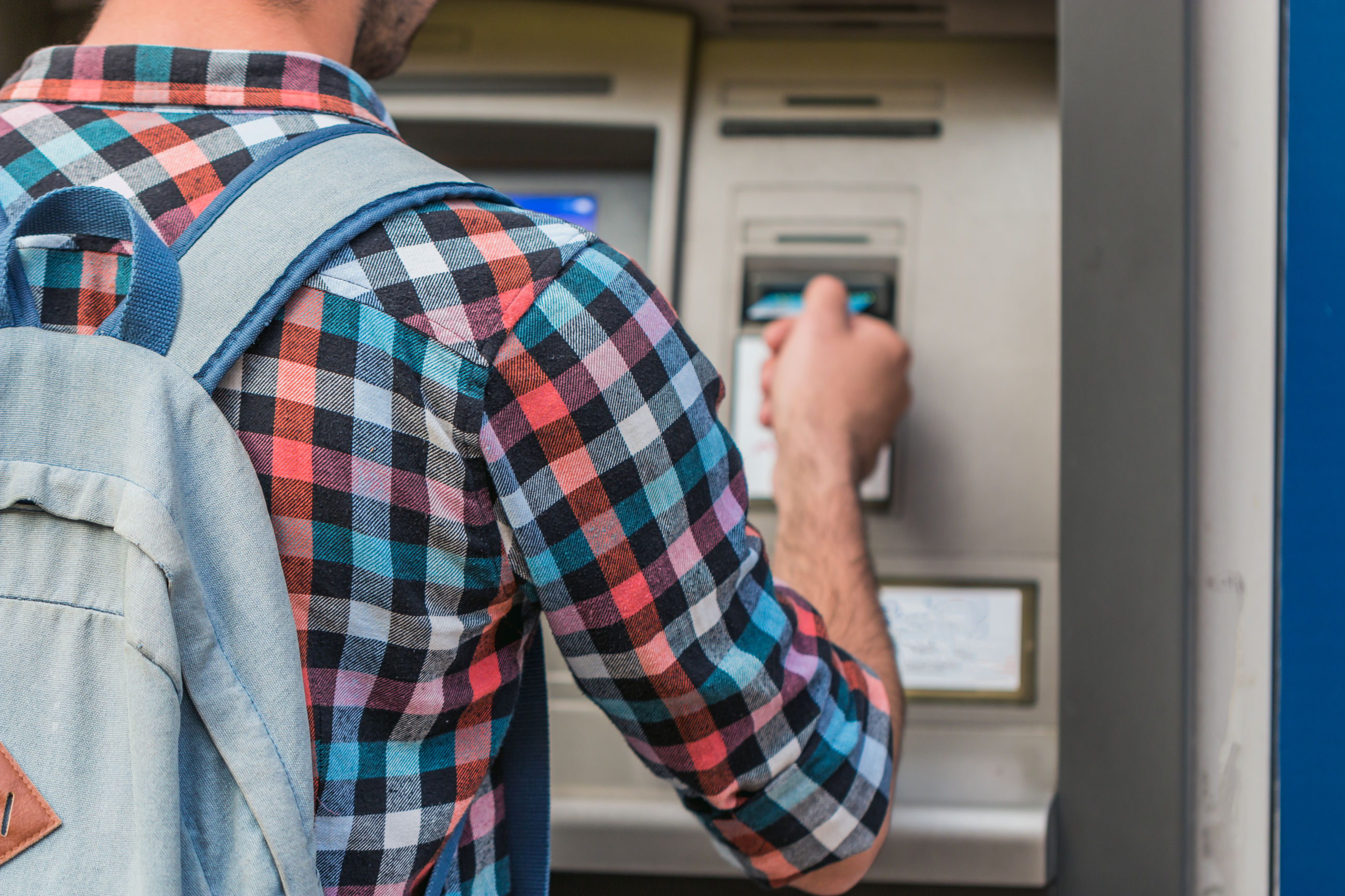 Rear view of man using atm machine