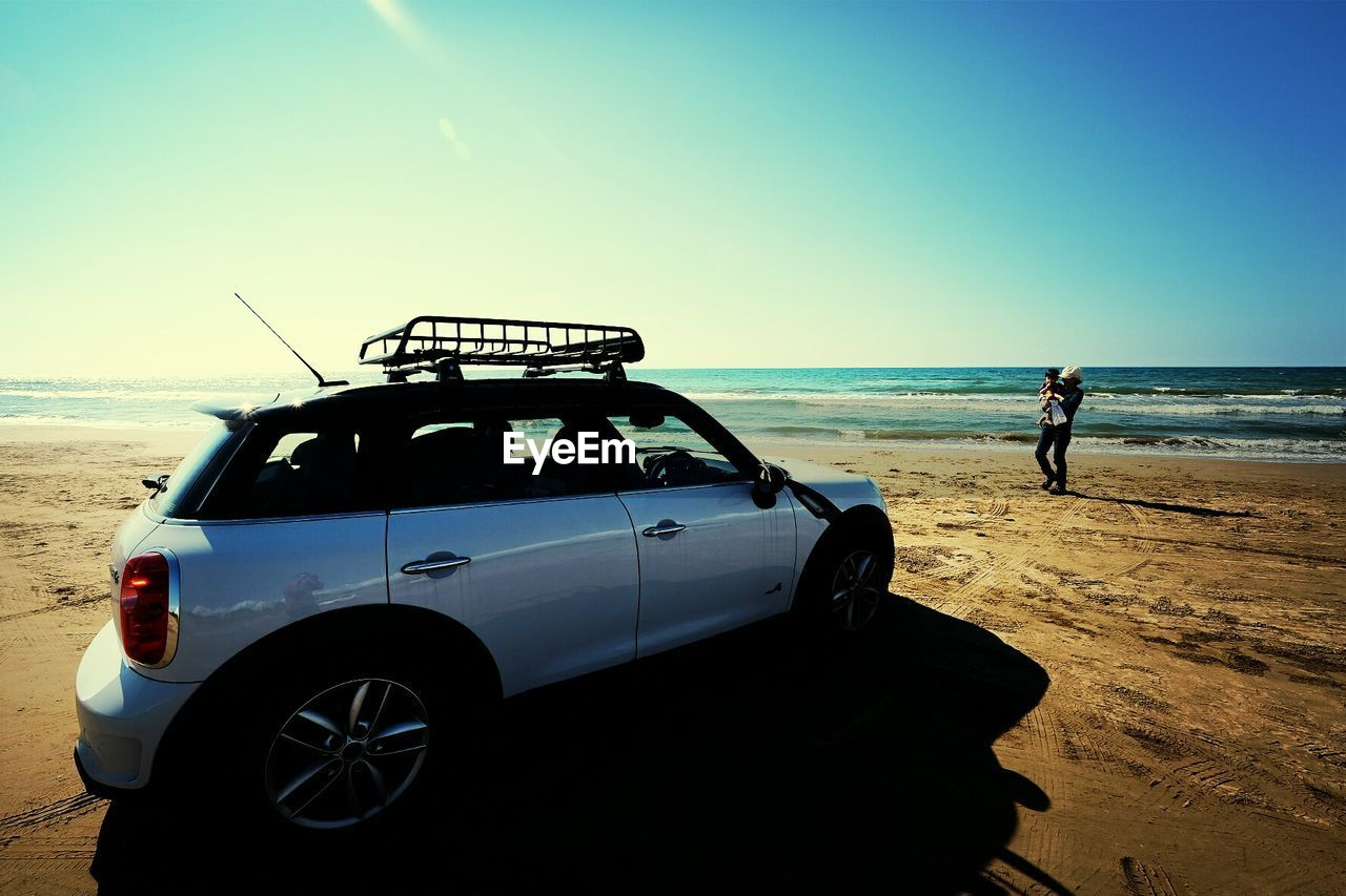 Man With Baby On Beach, Car In Foreground