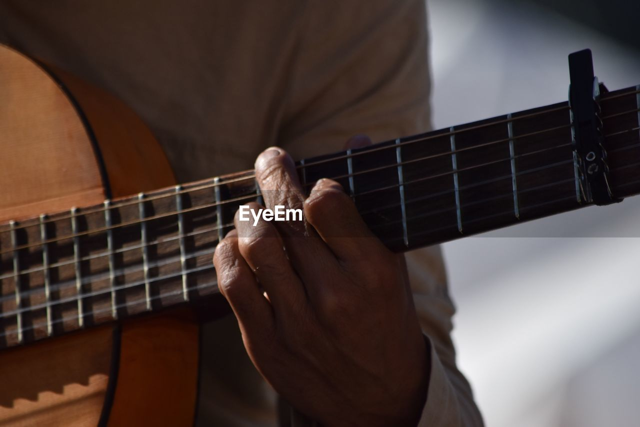 music, musical instrument, guitar, playing, human hand, musical instrument string, musical equipment, acoustic guitar, fretboard, one person, arts culture and entertainment, plucking an instrument, musician, leisure activity, real people, indoors, string instrument, focus on foreground, human body part, men, skill, close-up, electric guitar, day