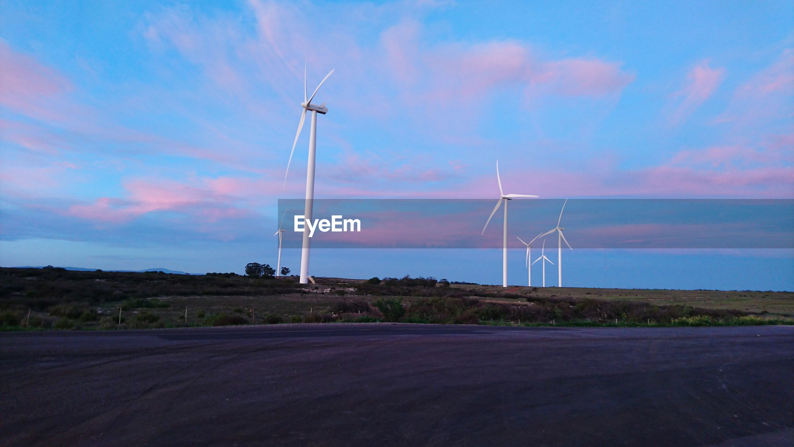 Wind turbines on landscape against cloudy sky