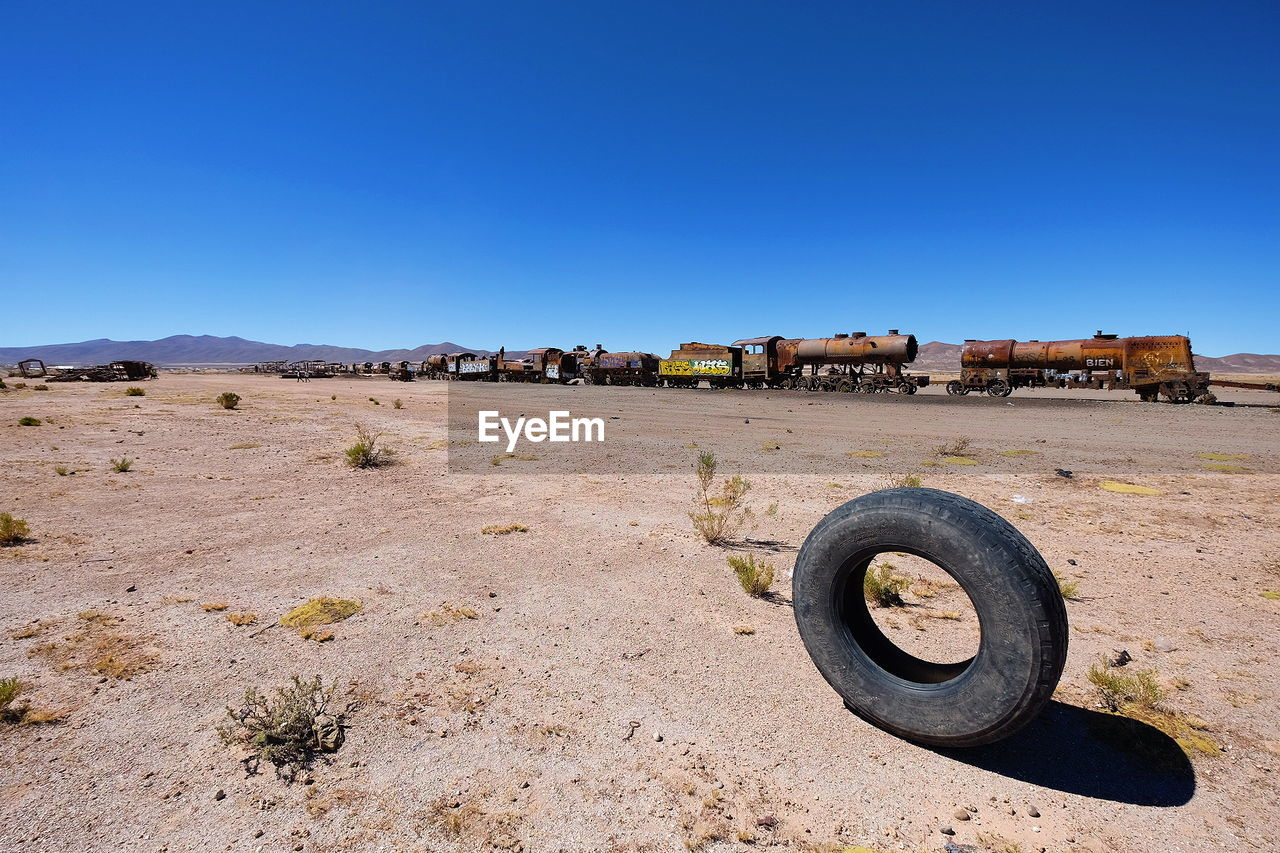 sky, clear sky, blue, copy space, land, nature, day, wheel, no people, sunlight, rusty, architecture, metal, field, abandoned, old, outdoors, landscape, obsolete, built structure, tire, deterioration