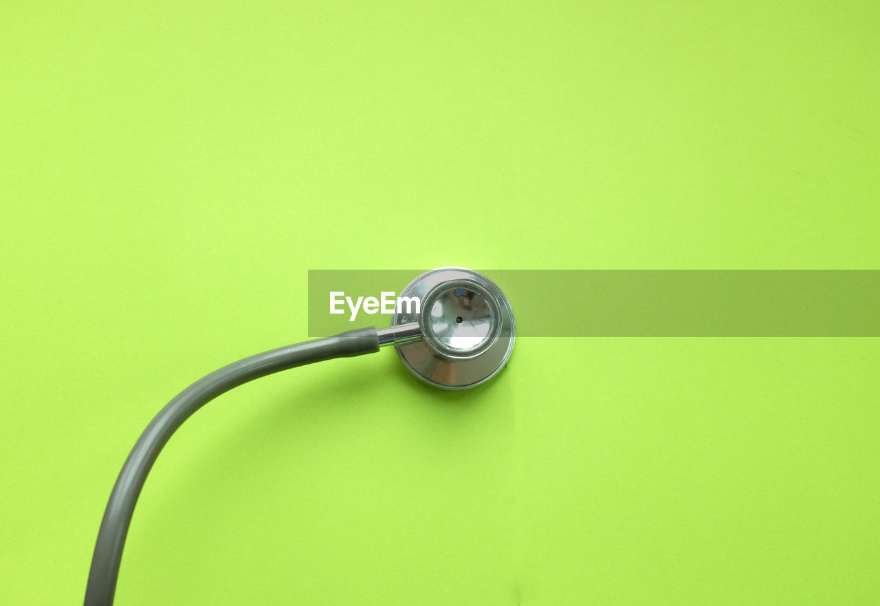 stethoscope, medical instrument, medical supplies, colored background, copy space, green color, medical equipment, no people, close-up, indoors, single object, green background, still life, studio shot, technology, cable, equipment, cut out, healthcare and medicine, metal, turquoise colored