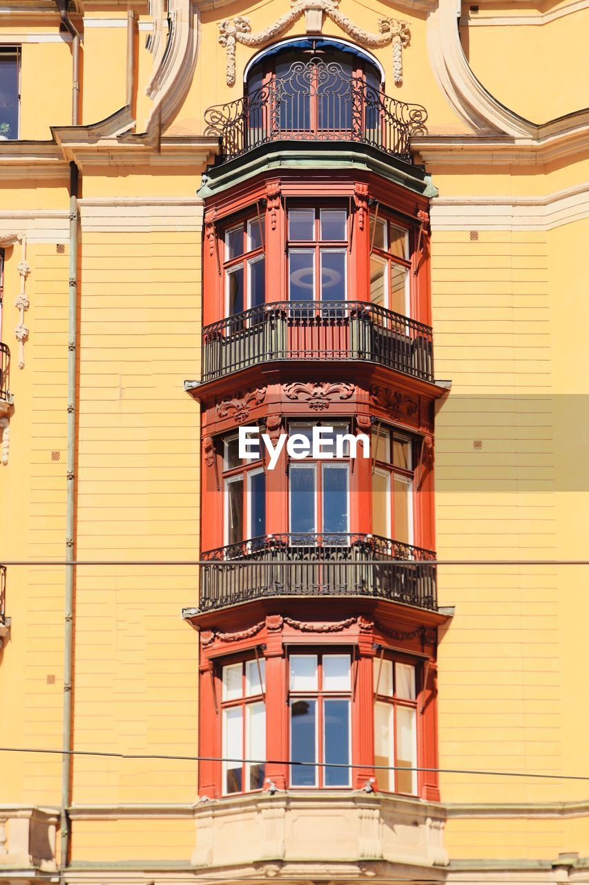 built structure, building exterior, architecture, building, low angle view, window, no people, residential district, day, balcony, outdoors, railing, city, yellow, wall - building feature, orange color, nature, staircase, house, arch, apartment