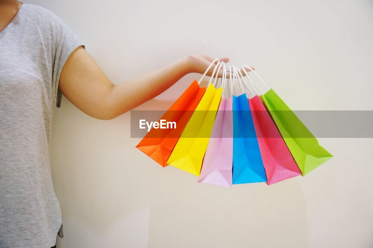 Midsection Of Woman Holding Colorful Shopping Bags Against White Background