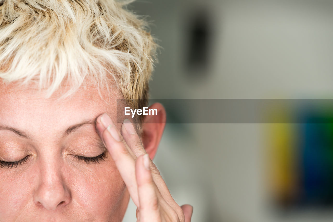 Close-up of blond woman with headache