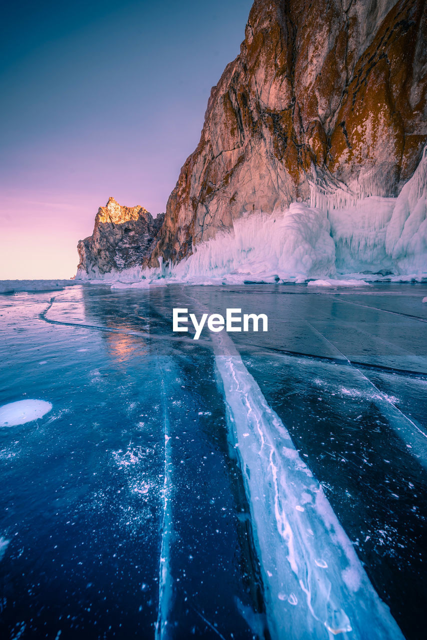 Scenic view of frozen lake by rock formation during sunset