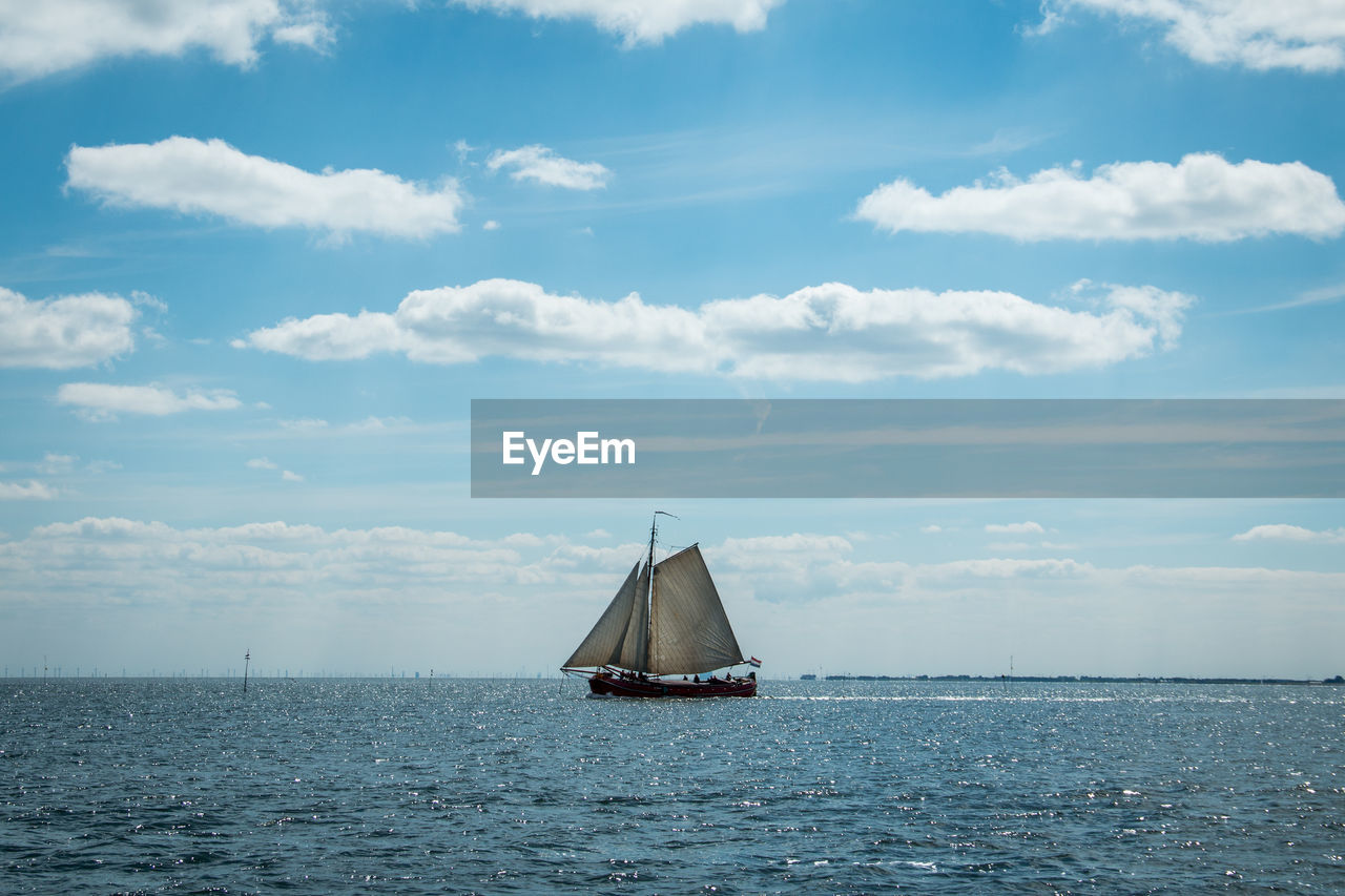 Sailboat On Seascape Against Sky