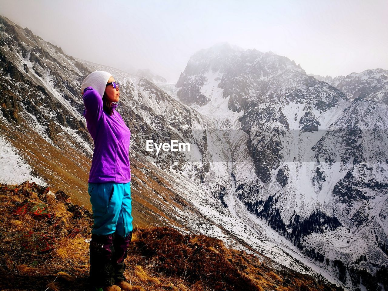 Side View Of Female Hiker Standing On Mountain During Winter