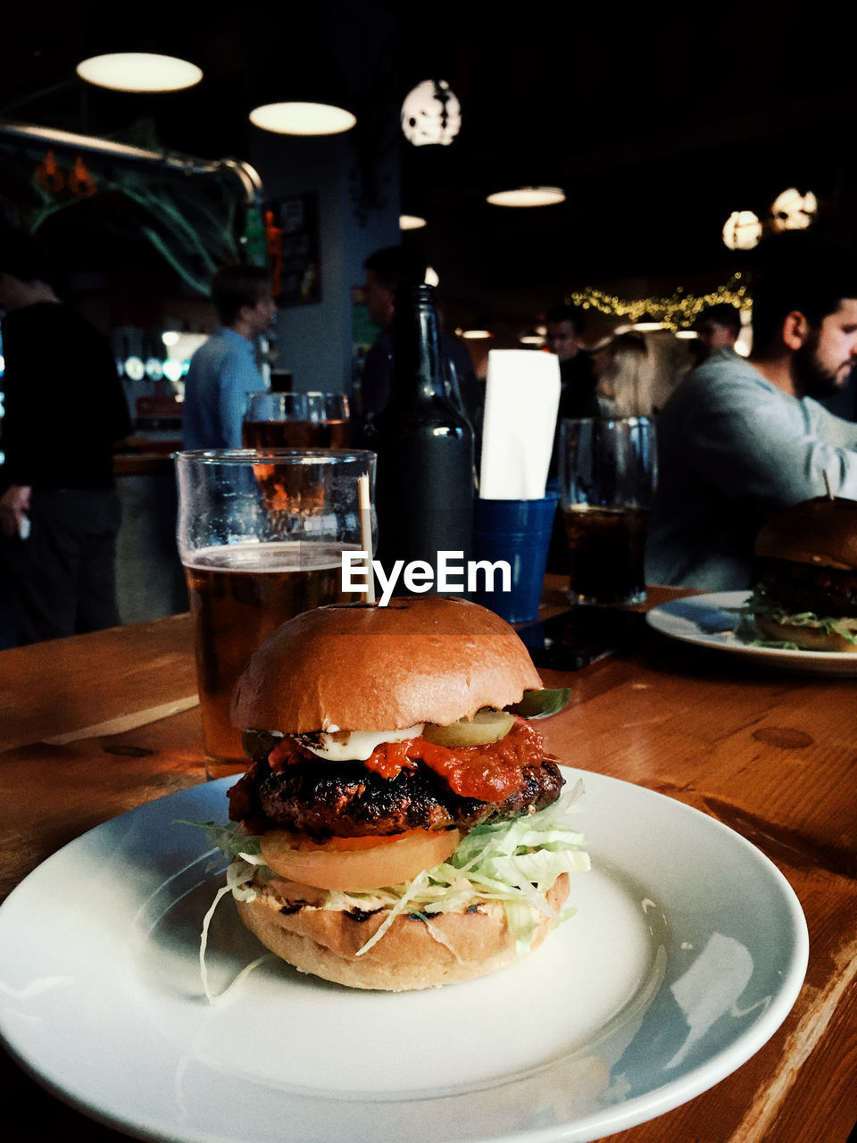 food and drink, burger, fast food, unhealthy eating, food, sandwich, table, incidental people, ready-to-eat, plate, restaurant, indoors, hamburger, freshness, drink, business, close-up, focus on foreground, indulgence, glass, temptation, snack