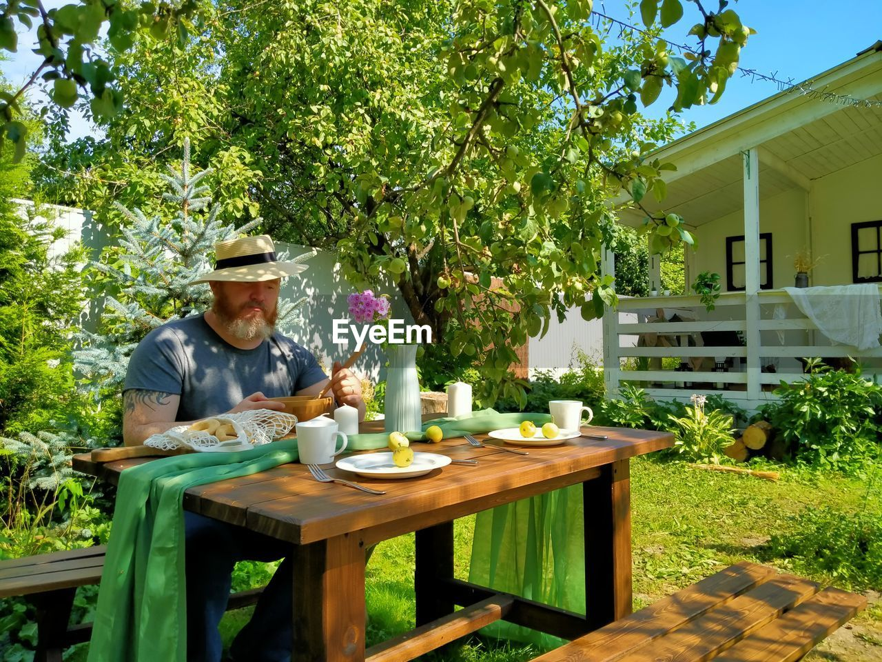 VIEW OF MAN SITTING ON TABLE AGAINST PLANTS