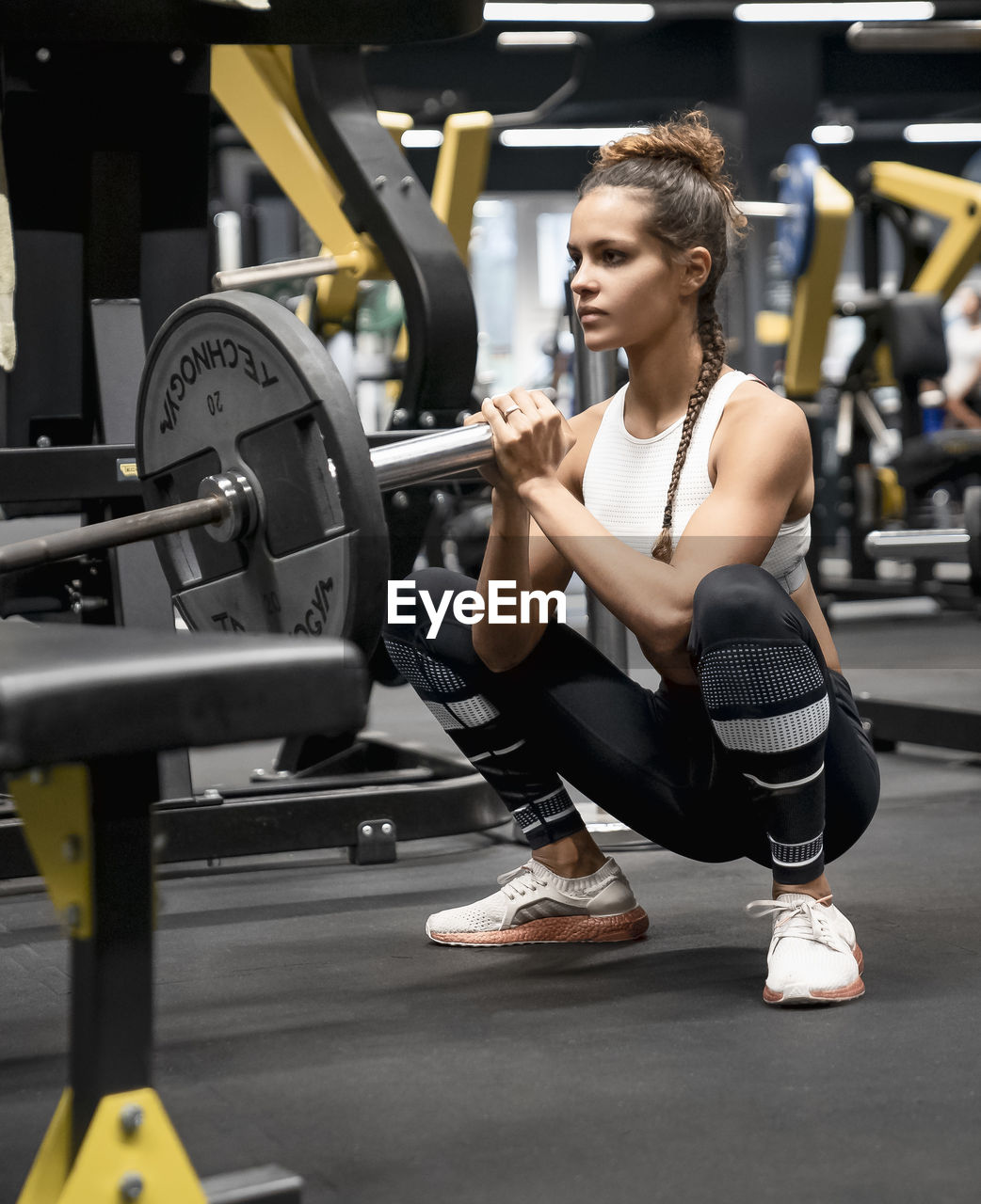gym, exercising, strength, sports training, sport, healthy lifestyle, muscular build, weight, health club, weight training, exercise equipment, one person, indoors, full length, body conscious, sports clothing, real people, weights, wellbeing, young adult, equipment, dumbbell, effort, exercise machine, self improvement, physical activity