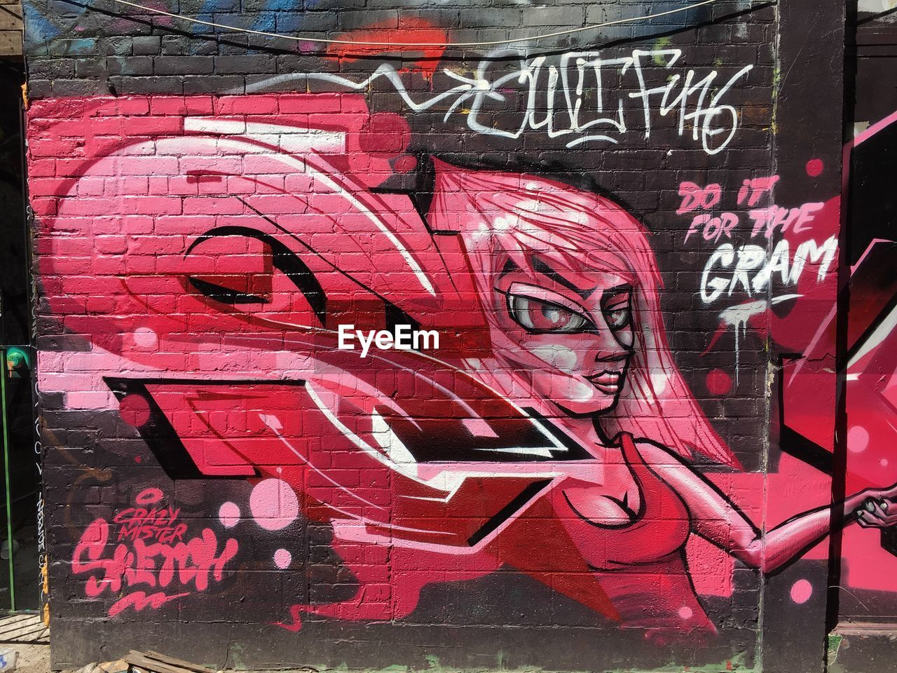 text, graffiti, communication, western script, red, one person, day, real people, creativity, art and craft, outdoors, pink color, representation, wall - building feature, lifestyles, sign, portrait, architecture, human representation, message