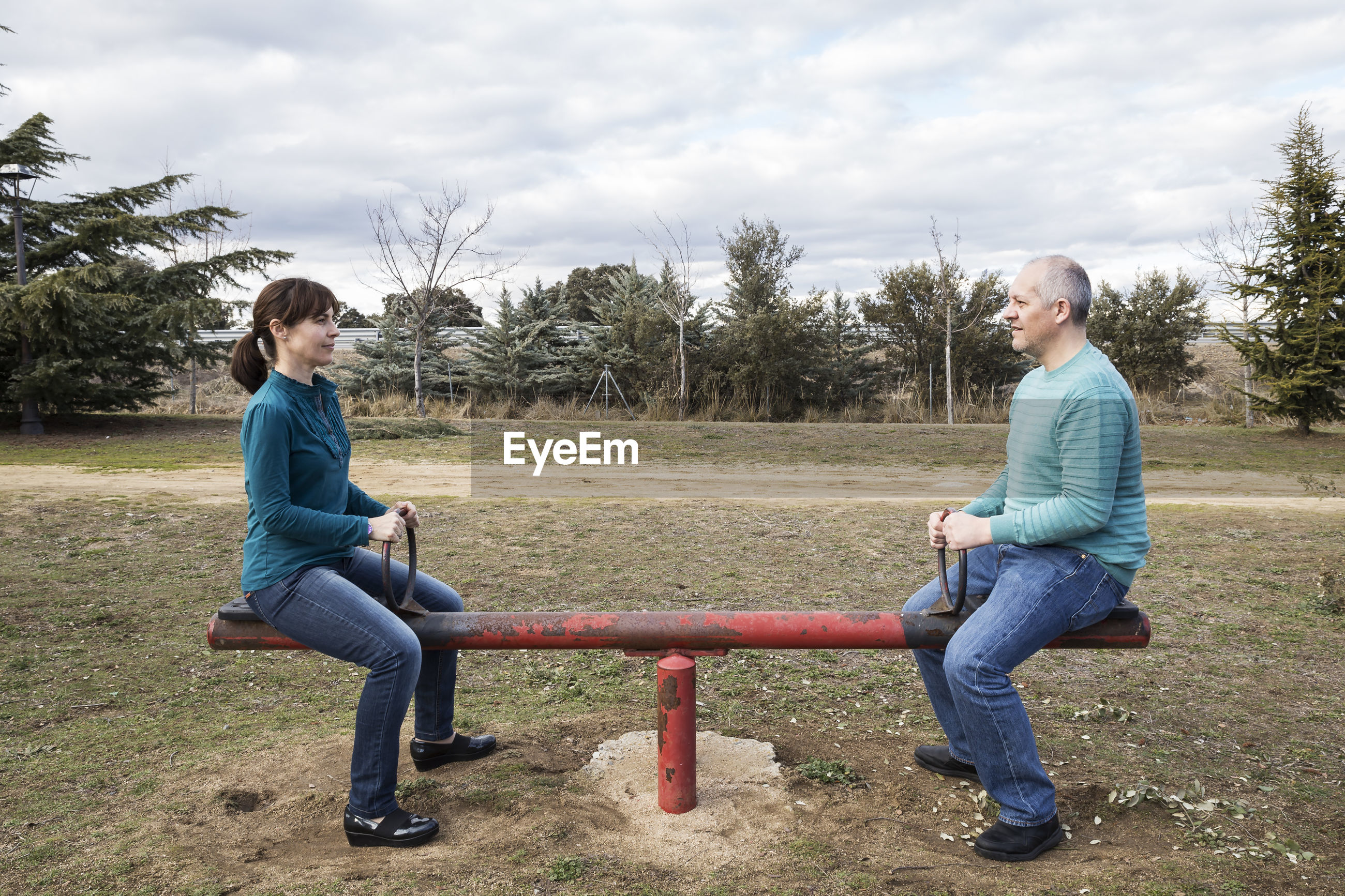 Woman and man mounted on a seesaw maintaining equality
