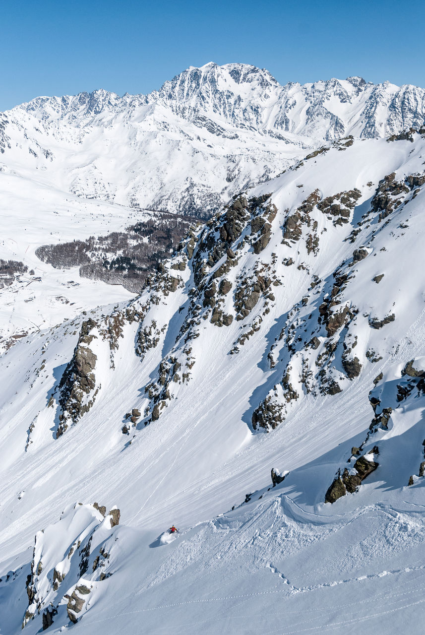 Scenic view of snowcapped mountains against sky and ski freerider descents from the mountain