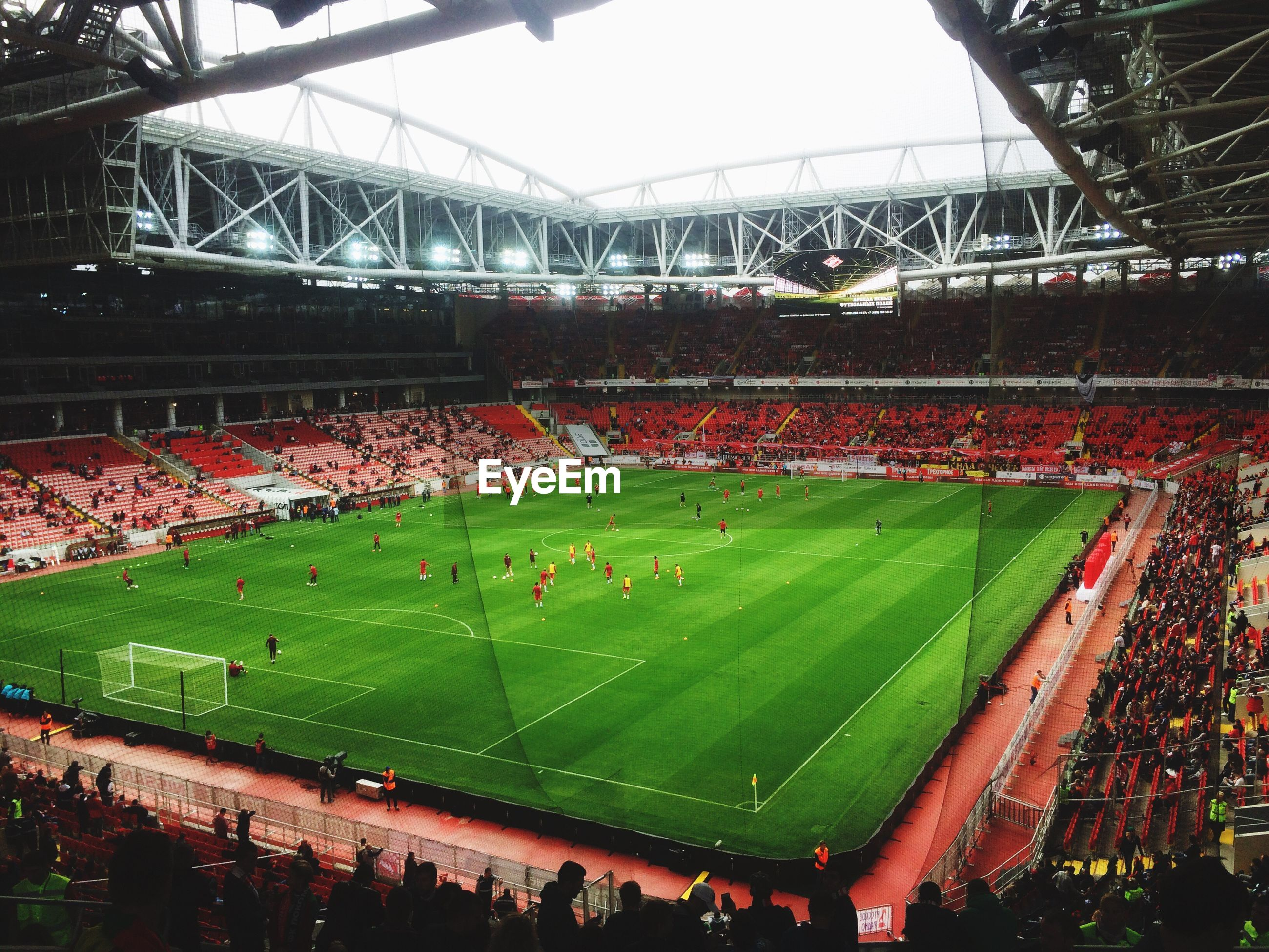 large group of people, high angle view, stadium, green color, built structure, architecture, competition, sport, teamwork, city life, togetherness, competitive sport, green, yard, crowd, day, repetition, outdoors, sportswear, spectator, architectural feature