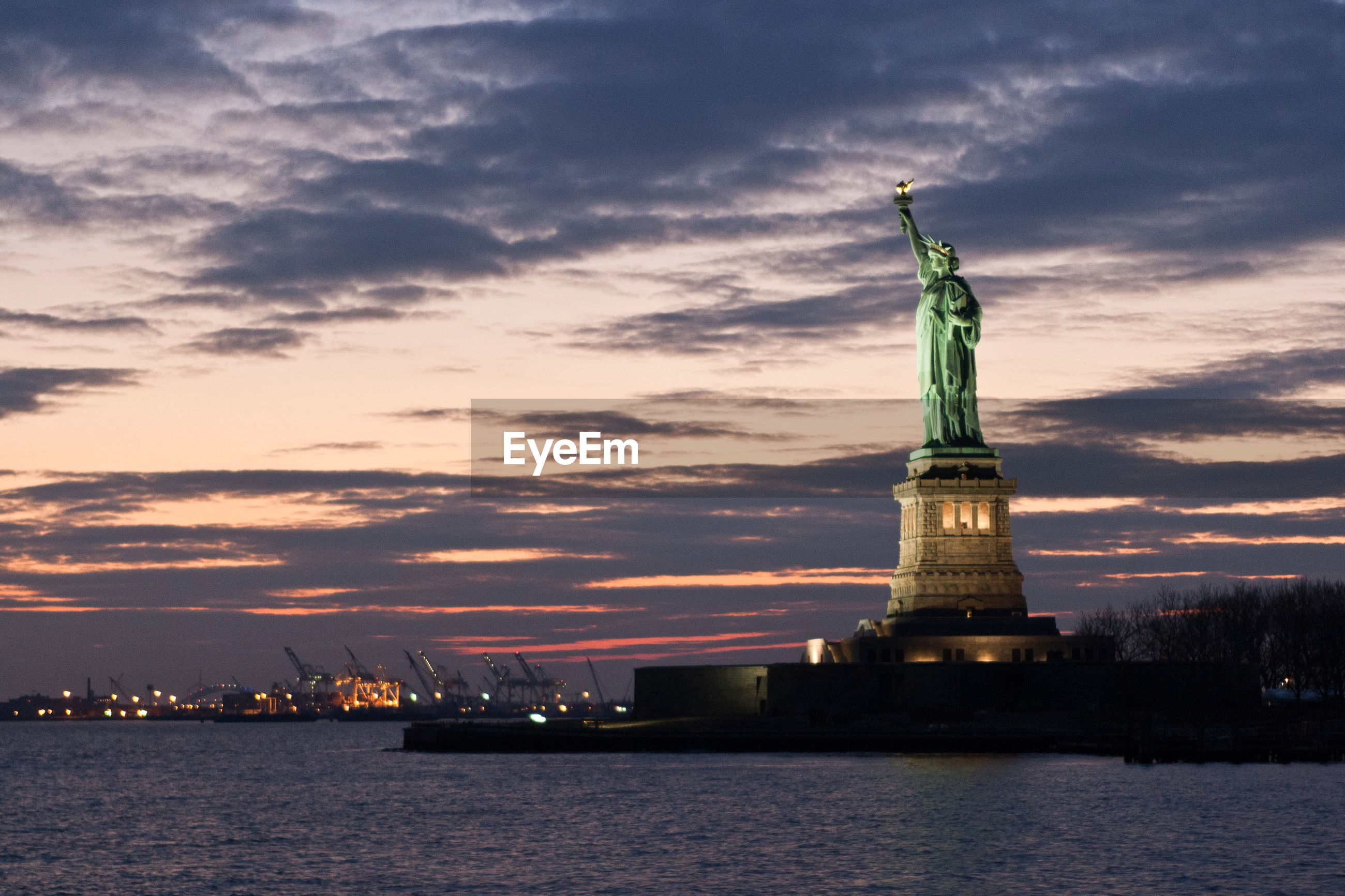 Statue of liberty against cloudy sky at dusk