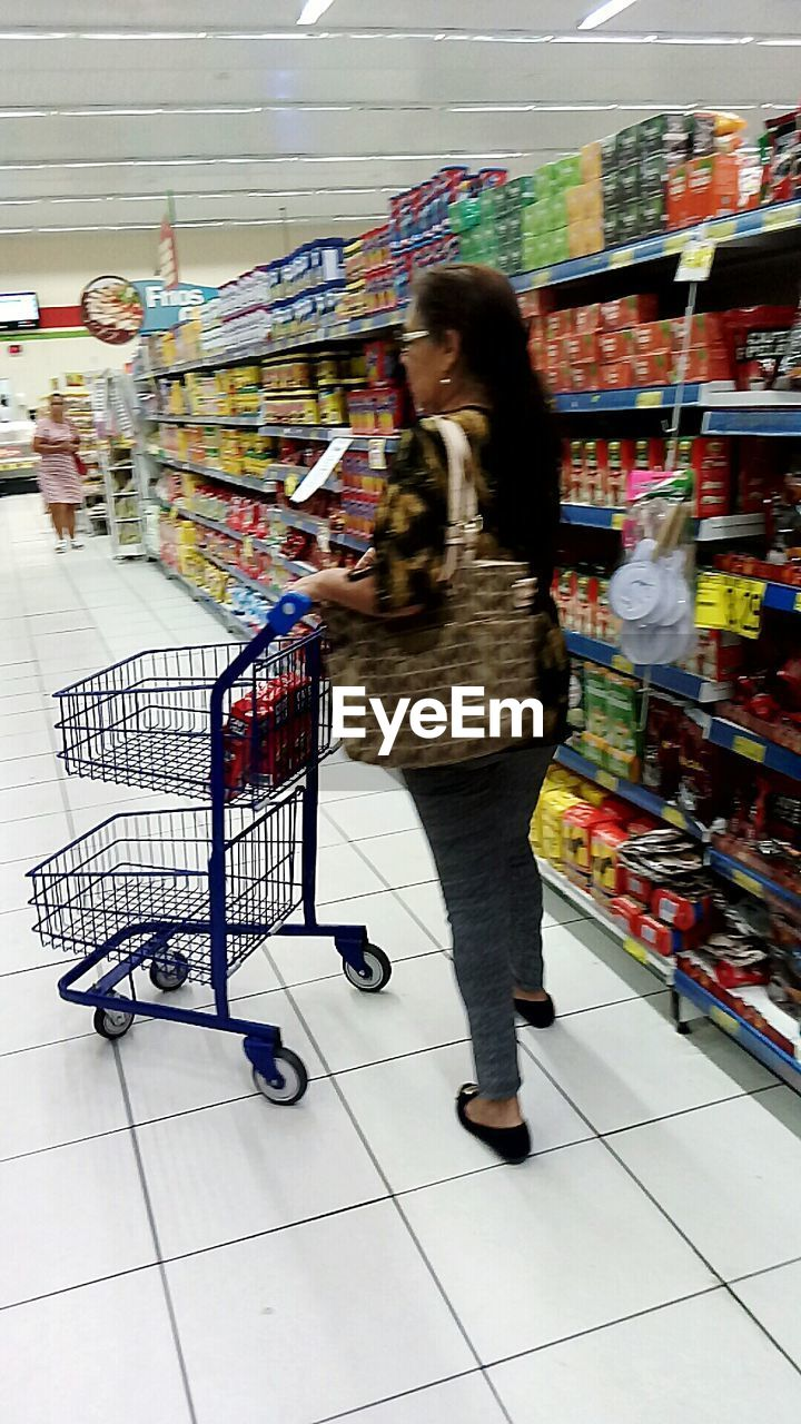 shopping cart, supermarket, consumerism, retail, customer, groceries, full length, buying, store, trolley, lifestyles, market, indoors, choice, merchandise, shelf, motion, one person, blurred motion, food and drink, standing, convenience, day, young adult, adult, people