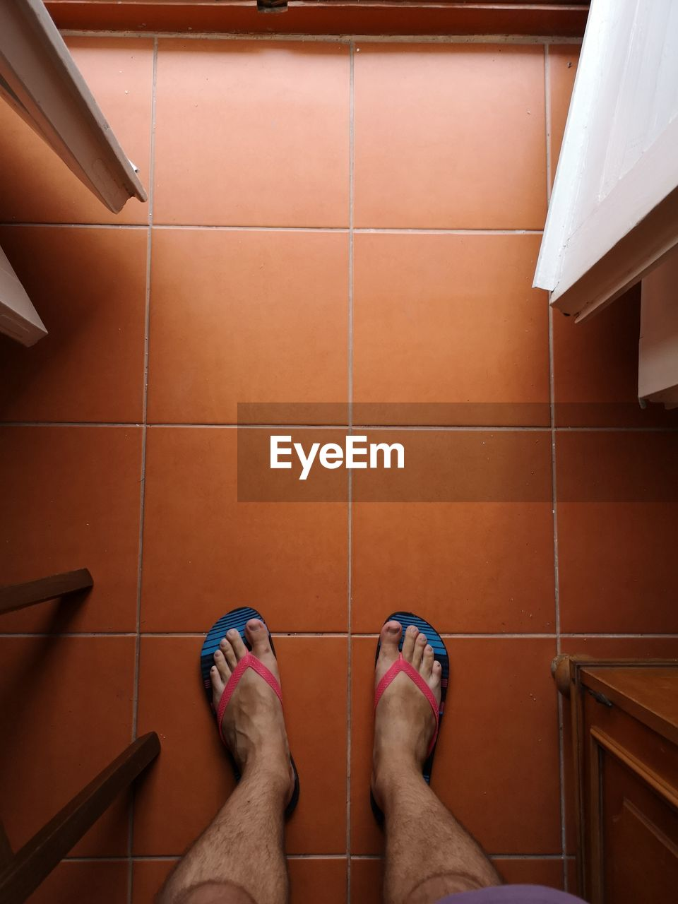low section, flooring, human leg, tile, body part, one person, human body part, indoors, personal perspective, shoe, real people, human foot, tiled floor, standing, barefoot, high angle view, lifestyles, directly above, bathroom, human limb, jeans
