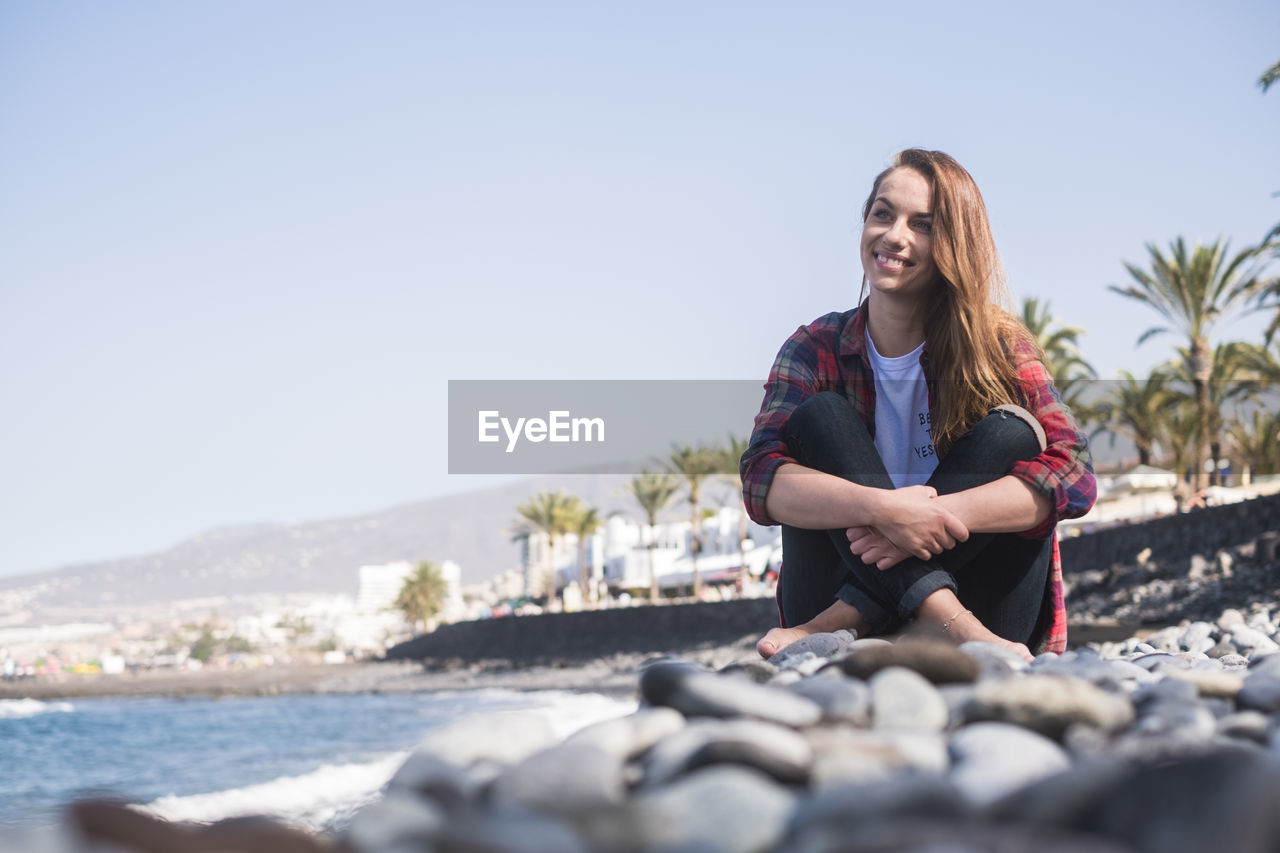 Smiling woman sitting on pebbles against clear sky