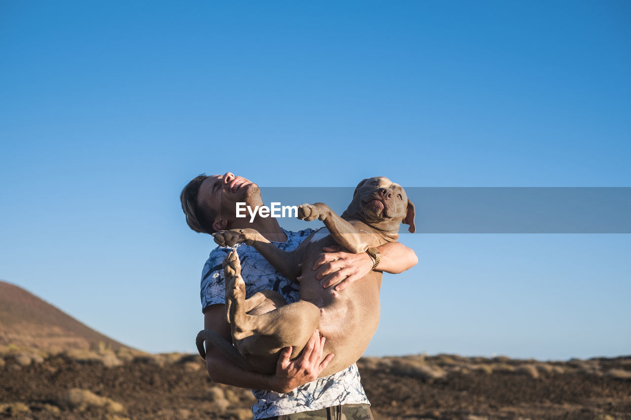 Young Man With Eyes Closed Holding Dog On Field Against Clear Blue Sky