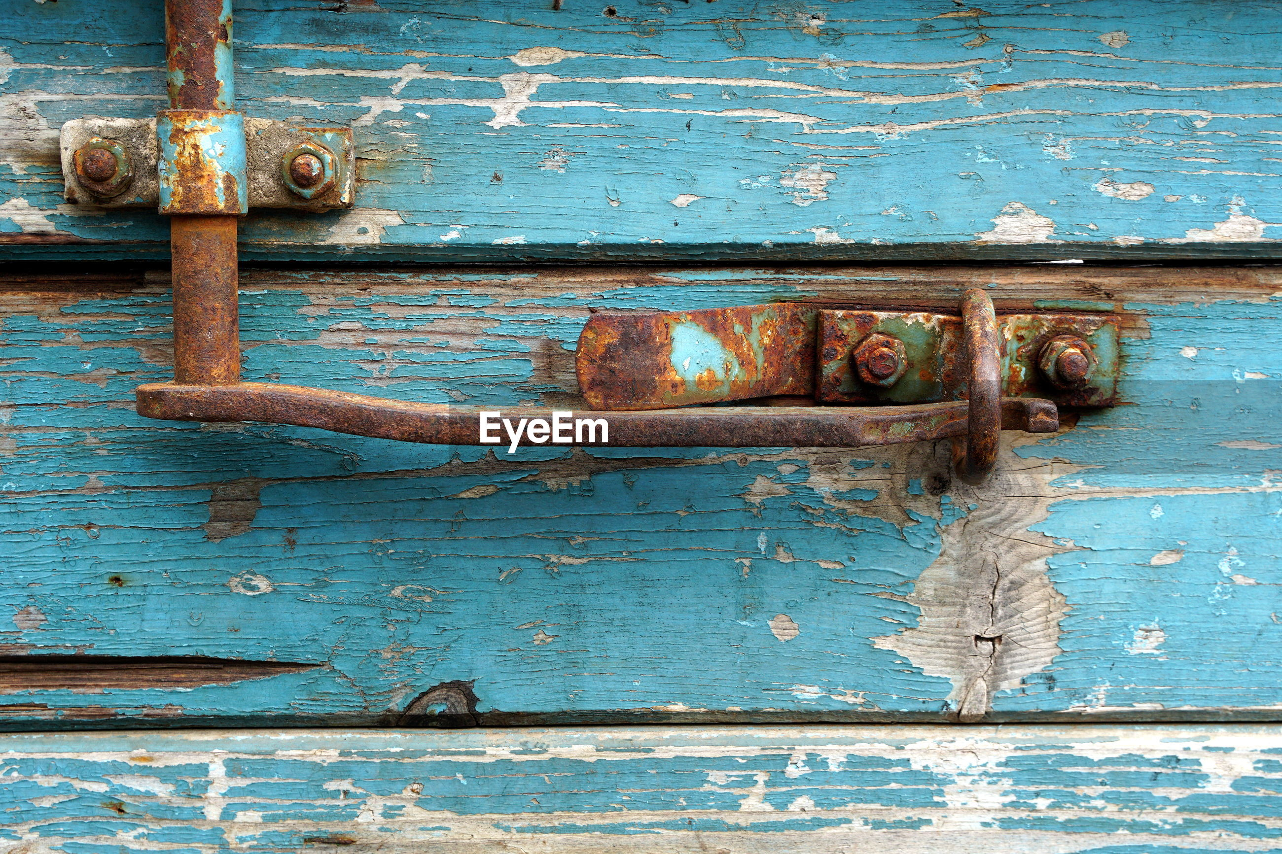 FULL FRAME SHOT OF RUSTY METAL DOOR WITH OLD WEATHERED WOODEN WALL