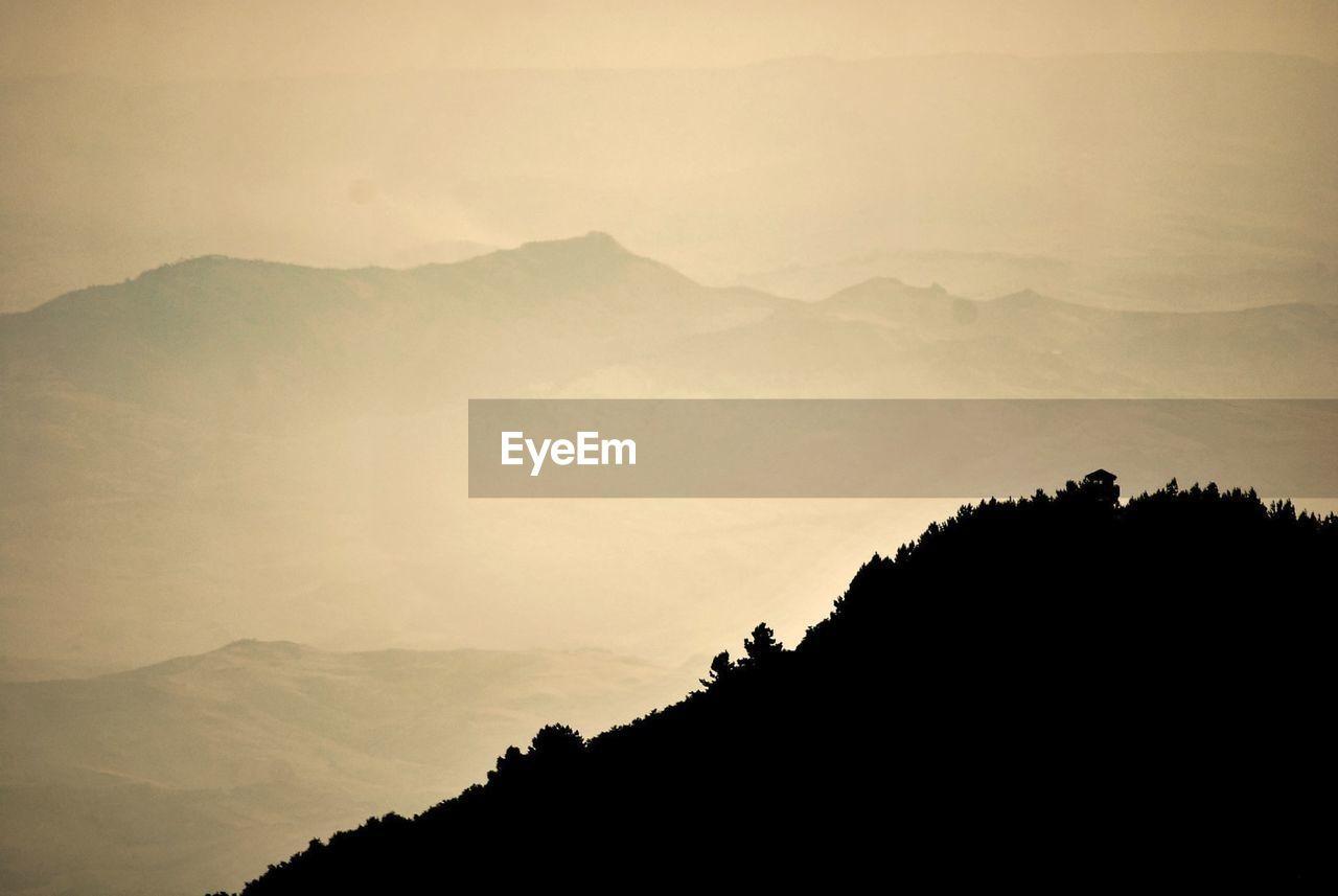 mountain, beauty in nature, silhouette, scenics - nature, tranquil scene, tranquility, sky, mountain range, environment, nature, tree, landscape, non-urban scene, cloud - sky, no people, fog, plant, idyllic, outdoors, mountain peak