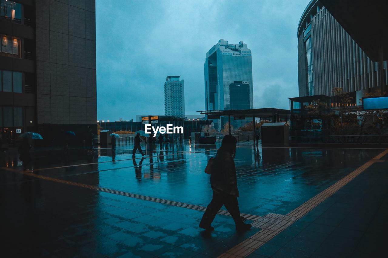 Man Walking On Street In City During Rainy Season