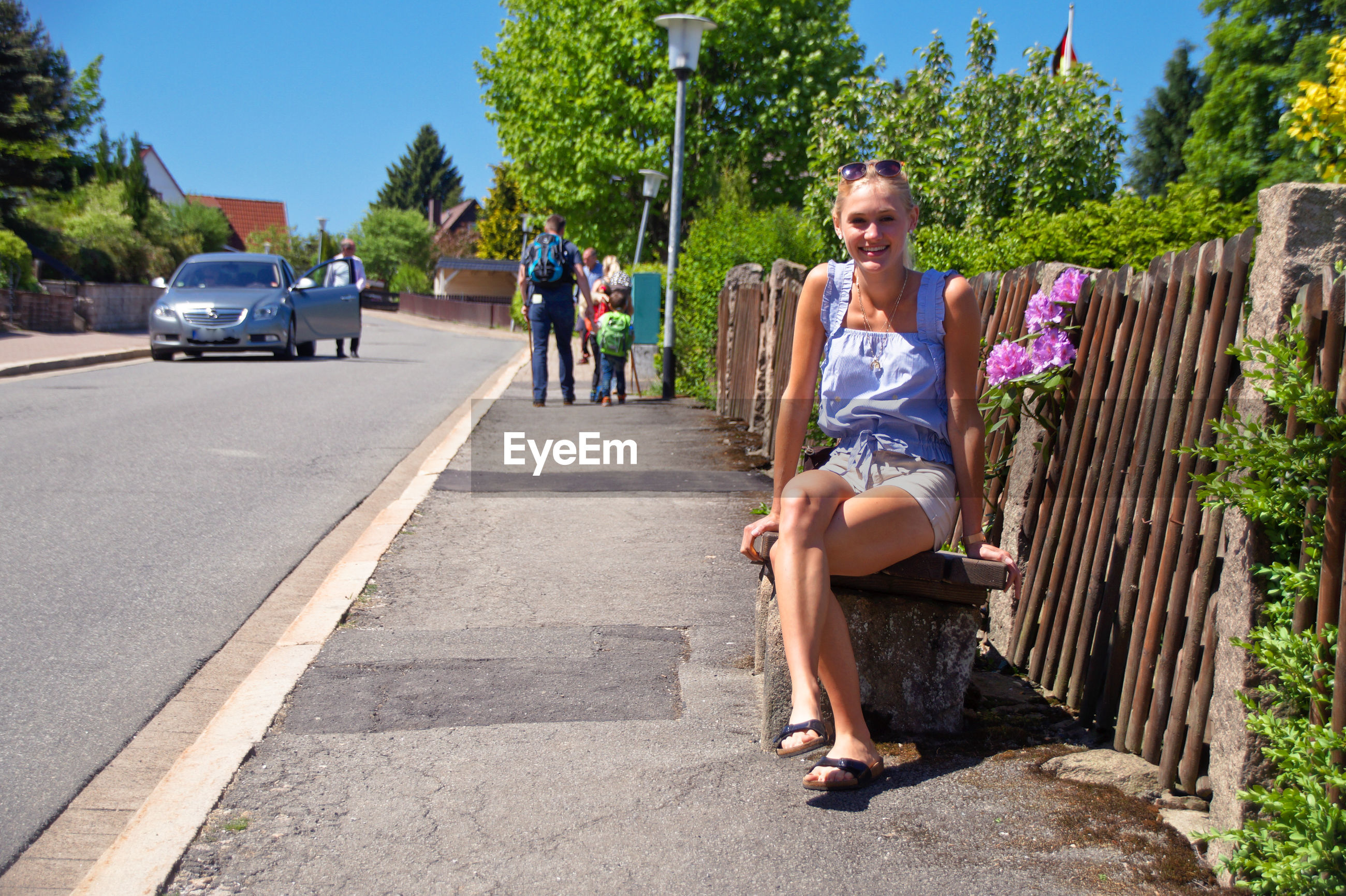 Full length portrait of young woman on seat at roadside during sunny day