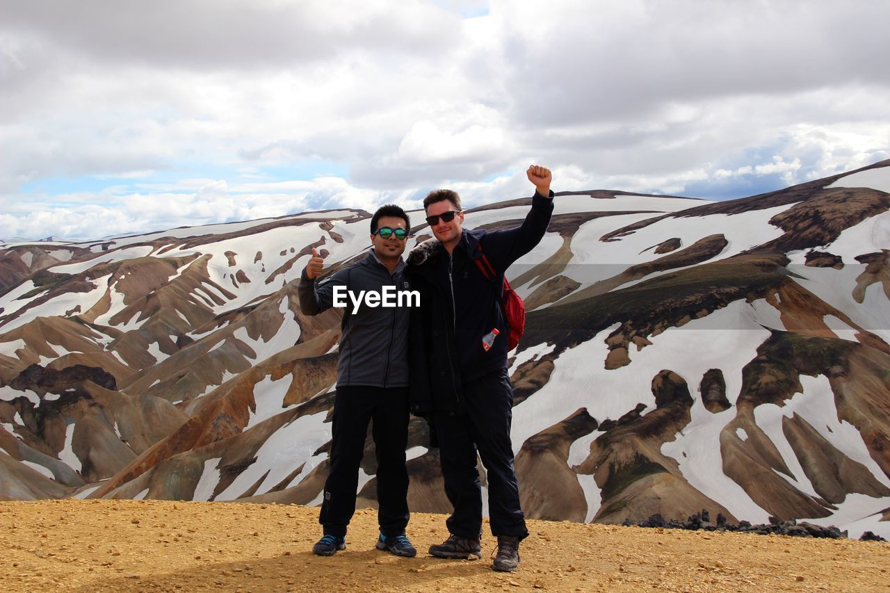 Full length of man with friend showing thumbs up sign against mountain during winter