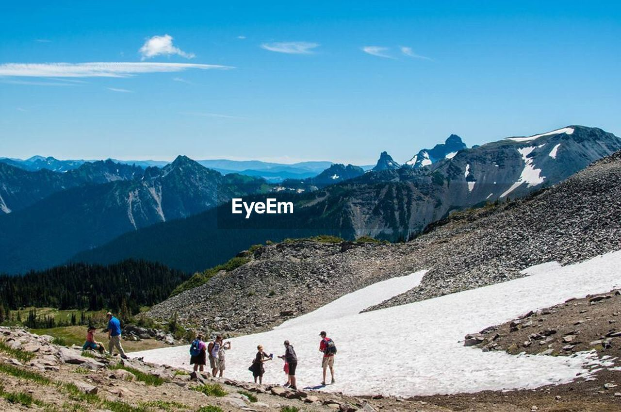 mountain, real people, mountain range, nature, beauty in nature, adventure, leisure activity, sky, tranquil scene, scenics, vacations, lifestyles, men, day, tranquility, outdoors, landscape, hiking, women, travel destinations, snow, cold temperature, physical geography, sport, large group of people, people