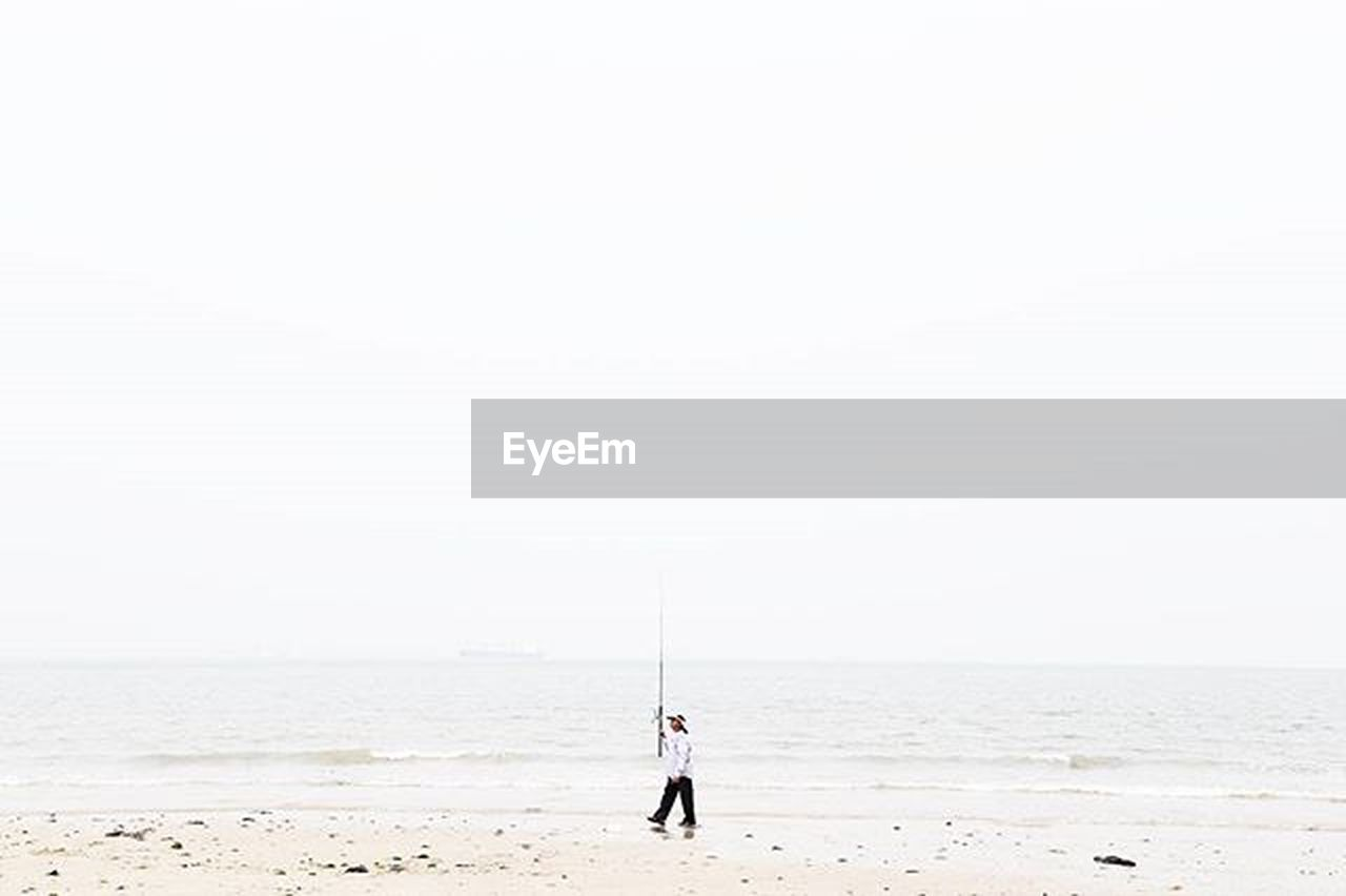sea, beach, copy space, horizon over water, full length, standing, nature, one person, outdoors, sand, vacations, tranquil scene, tranquility, day, clear sky, adult, water, one man only, people, scenics, sky, adults only, paddleboarding, human body part, only men, beauty in nature